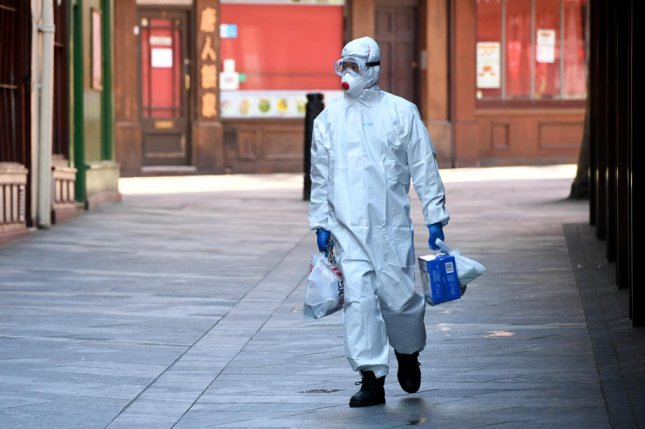 A man wearing a protective suit walks in central London, Britain, on May 2. Photo by Facundo Arrizabalaga/EPA-EFE