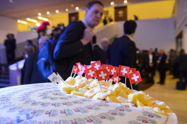 Attendees of the posh World Economic Forum in Davos, Switzerland, walk past a spread of Swiss cheese during a panel session in 2015. President-elect Donald Trump's transition team said Trump is not sending a representative to the annual gathering because it would betray his populist agenda. File photo by Jean-Christophe Bott/European Pressphoto Agency