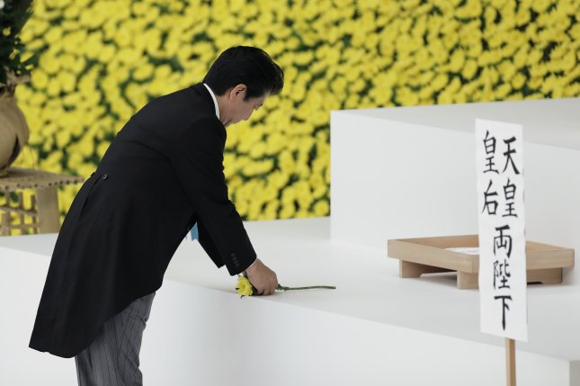 Japanese Prime Minister Shinzo Abe lays a flower Thursday at a memorial service in Tokyo commemorating the 74th anniversary of Japan's surrender in World War II. Photo by Kiyoshi Ota/EPA-EFE