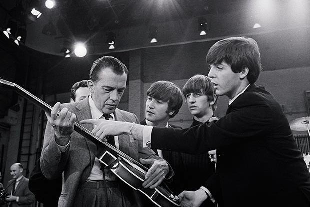 Paul McCartney (R) shows Ed Sullivan (L) his guitar during a rehearsal for the debut of the Beatles on The Ed Sullivan Show on February 9, 1964. The Beatles made waves during that first U.S. visit and two years later would make headlines again when John Lennon (second from left) said the British band was more popular than Jesus. The remarks prompted backlash from Americans, some of whom went on to boycott the wildly popular band and burn its albums. UPI File Photo