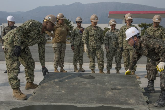 U.S. Navy Utilitiesman 3rd Class Brandon Matthews, from Charleston, South Carolina, assigned to Naval Mobile Construction Battalion (NMCB) 4, and his Republic of Korea (ROK) Naval Mobile Construction Battalion counterpart install a ramp plate on an expeditionary airfield. Key Resolve, a computer-simulated training exercise, involved for the first time the application of a new operation plan, OPLAN 5015. (U.S. Navy combat camera photo by Mass Communication Specialist 1st Class Charles E. White/Released)