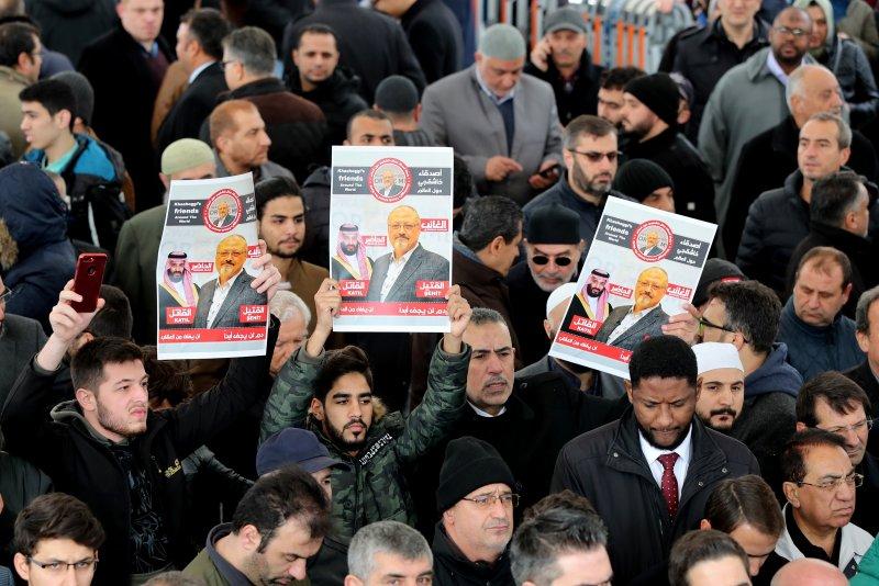 People hold photos of slain Saudi journalist Jamal Khashoggi Friday as they pray at the Fatih Mosque in Istanbul, Turkey. Photo by Tolga Bozoglu/EPA-EFE