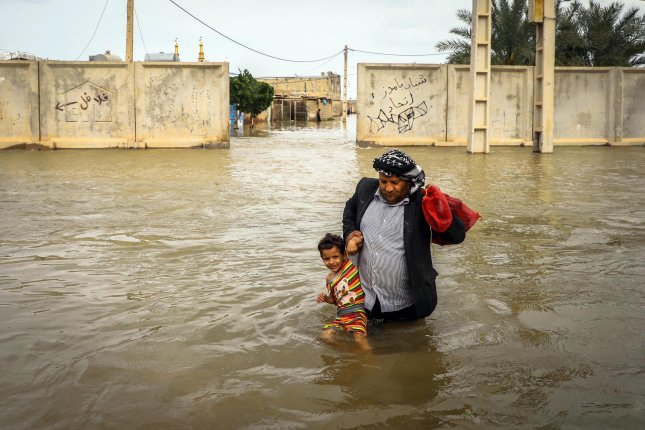 An Iranian man carries his son in a flooded village around the city of Ahvaz, Khuzestan province, Iran, on Sunday. Photo by Mehdi Pedramkhoo/EPA-EFE
