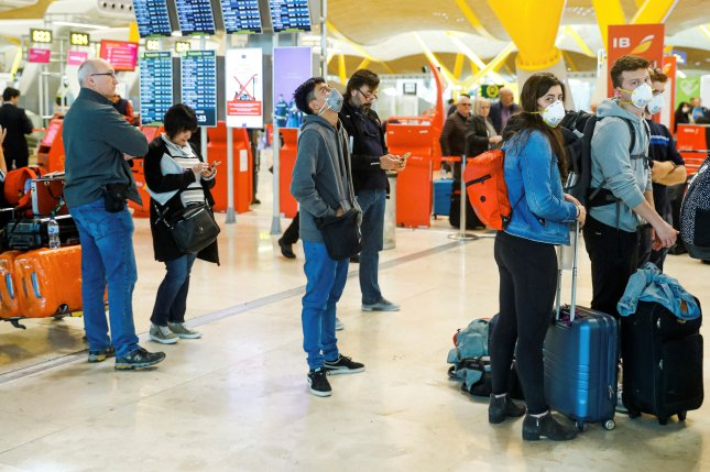 Travelers stand in line at the Adolfo-Suarez Barajas International Airport in Madrid on March 12, 2020. Photo by Emilio Naranjo/EPA-EFE