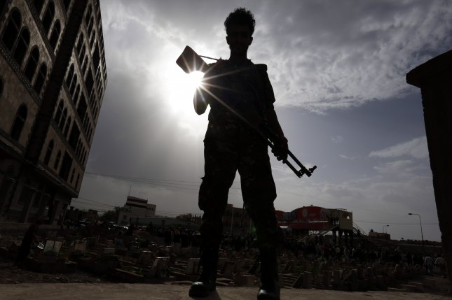 A Yemeni soldier stands guard as people bury bodies of Houthi rebels in the capital, Sanaa. A Saudi-led coalition targeted Houthis in Yemen's critical Red Sea port Wednesday. Photo by Yahya Arhab/EPA-EFE