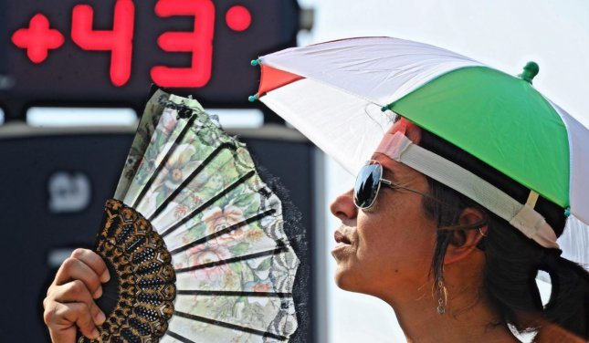 A woman fans her self to cool down from the European heatwave. File Photo by Maurizio Degl' Innocenti/EPA