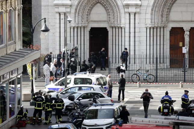 French police stand at the entrance of the Notre Dame Basilica church in Nice, France, on Thursday following a knife attack that killed at least three people. The suspect was wounded by police. Photo by Sebastien Nogier/EPA-EFE