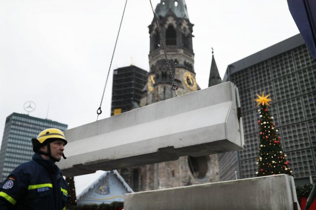 Concrete barriers are installed in front of the Breitscheidplatz square in Berlin ahead of the scheduled reopening of the Christmas Market on Thursday. A truck attack on the market on Monday killed at least 12 people and injured another 49. Photo by Michael Kappeler/European Pressphoto Agency