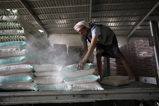 A worker stacks grain inside a warehouse in Sana'a, Yemen, on July 19. Tuesday's report says Yemen has the world's largest needy population. File Photo by Yahya Arhab/EPA-EFE