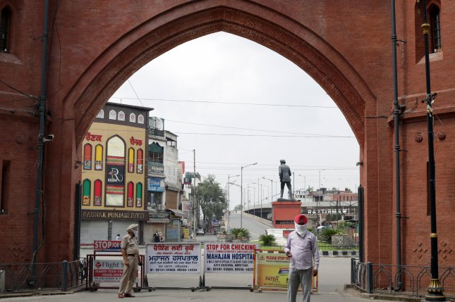 A Punjab police officer stands near barricades installed at the Gandhi Gate, during the weekend lockdown in Amritsar, India, on Sunday Another lockdown was imposed by the state government to control the spread of COVID-19. Photo by Raminder Pal Singh/EPA-EFE