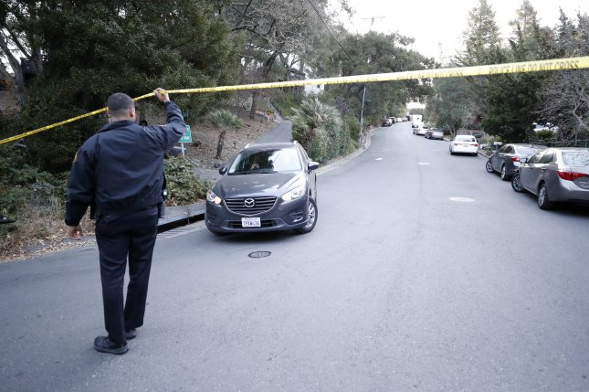 An Orinda, Calif., police officer lets a resident's car pass through the police line tape near the scene where five people were killed during a Halloween Party shooting at an Airbnb rental house. Photo by John G. Mabanglo/EPA-EFE