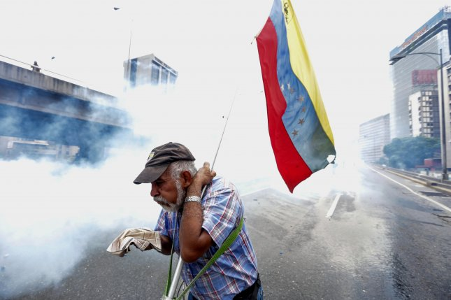 A protester tries to protect himself from tear gas during a protest in Caracas, Venezuela, on April 19. Photo by Cristian Hernandez/UPI