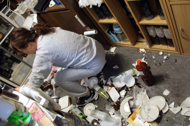 A woman cleans broken plates at a restaurant after a strong earthquake hit northeastern Japan, in Fukushima, northeastern Japan Saturday. Photo by Jiji Press/EPA-EFE