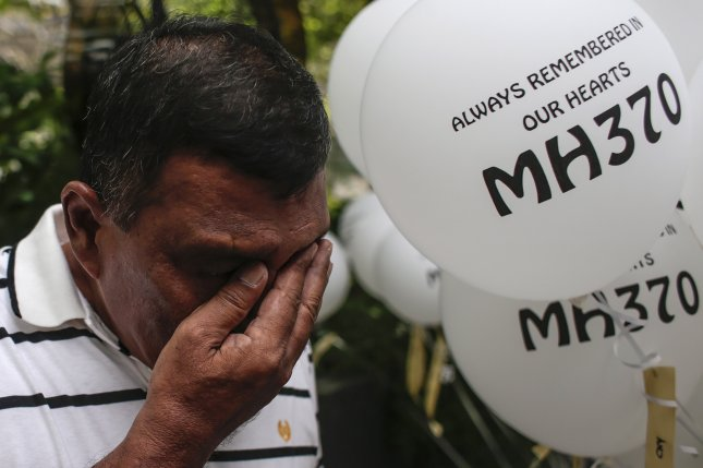 A family member of missing Malaysia Airlines Flight 370 passengers cries during a remembrance ceremony to mark the second anniversary of the plane's disappearance. Search for the aircraft, which disappeared March 8, 2014, is set to resume soon. Photo by Fazry Ismail/EPA
