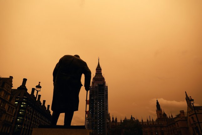 The sky turns orange over a statue of former Prime Minster Winston Churchill in Westminster in London on Monday. The remnants of Hurricane Ophelia pulled in tropical air, dust and debris from southern Europe and Africa to change the color of the sky. Photo by Neil Hall/EPA-EFE