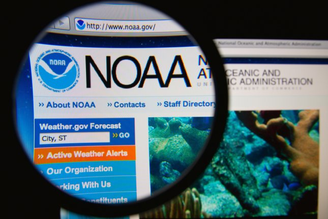 National Oceanic and Atmospheric Administration homepage through a magnifying glass. NOAA is a scientific agency focused on the conditions of the oceans and the atmosphere. The NOAA reported the National Weather Service's systems were hacked last month, a leak attributing the cyber attack to the Chinese. Gil C/Shutterstock.com
