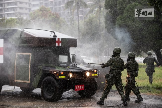 Troops spray chemicals onto a military vehicle on Monday during a simulated warfare drill in Tainan city, Taiwan. Photo by Taiwan Defense Ministry/EPA-EFE
