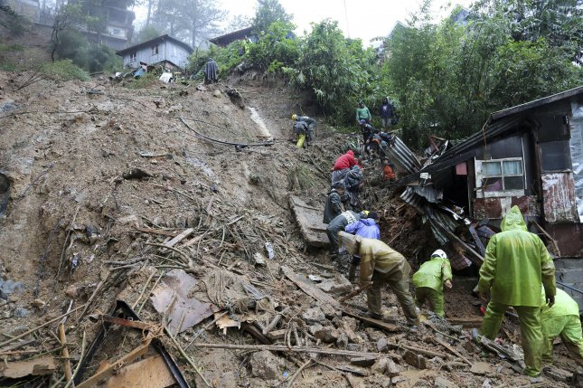 Rescuers, paramedics and volunteers conduct a search-and-retrieval operation to locate three missing people buried due to a landslide caused by typhoon Mangkhut at Balacbac, Baguio City, north of Manila, on Sunday. Photo by EPA