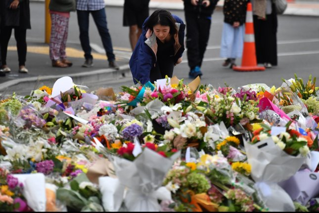 A mourner places flowers at a makeshift memorial Saturday near the Al Noor Masjid mosque in Christchurch, New Zealand. Photo by Mick Tsikas/EPA-EFE