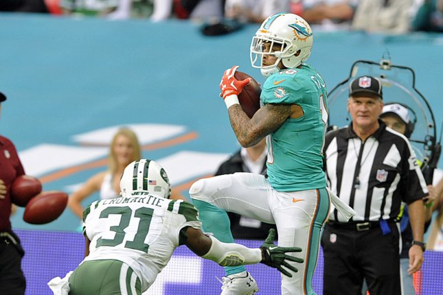Miami Dolphins wide receiver Kenny Stills (R) scores a touchdown against the New York Jets with Antonio Cromartie (L) during their NFL International series match at Wembley Stadium, London, Britain, 04 October 2015. EPA/GERRY PENNY