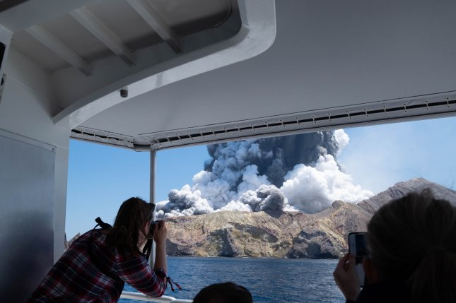 A visitor takes a photo of the White Island volcano as it erupts Monday, in the Bay of Plenty, New Zealand. Photo by Michael Schade/EPA-EFE