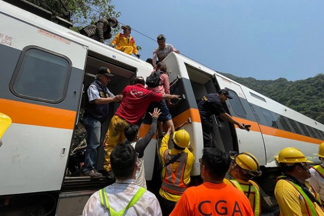 Passengers from a derailed train in Hualien County, eastern Taiwan, on Friday are seen leaving one of the cars with the aid of emergency personnel. Photo by Hualien Speedy News/EPA-EFE