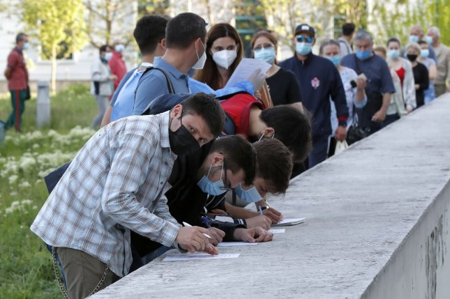 Romanians complete registry forms while lining up to get immunized against COVID-19 in Bucharest, Romania, on May 7. File Photo by Robert Ghement/EPA-EFE