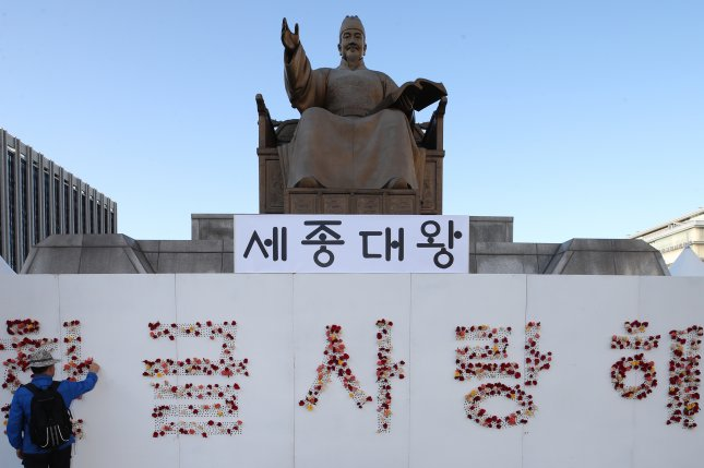 A citizen attaches a flower to a specially erected partition, with text reading Love Hangeul, in front of the King Sejong the Great statue in downtown Seoul as South Korea celebrates Hangeul Day on Wednesday. Photo by Yonhap