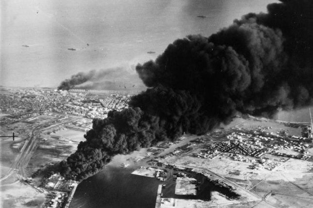 Smoke rises from oil tanks beside the Suez Canal hit during the initial Anglo-French assault on Port Said, 5 November 1956. File Photo courtesy Imperial War Museum