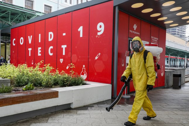 Russian Emergency Situations Ministry worker sanitizes Friday in front of the COVID-19 mobile laboratory on the Belorussky railway station in Moscow. Photo by Sergei Ilnitsky/EPA-EFE