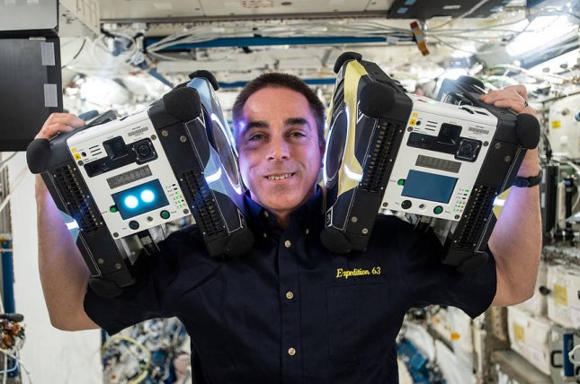 NASA astronaut Chris Cassidy poses with two Astrobee robotic assistants during visual and navigation tests aboard the International Space Station in 2020. Photo courtesy of NASA