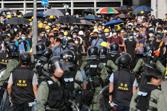 Protesters stand in front of police during a mass rally in Yuen Long, Hong Kong on Saturday. Photo by Ritchie B. Tongo/EPA