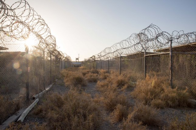 A walkway separates the two sides of the abandoned Camp X-Ray detention camp at the Guantanamo Bay Naval Base on July 23, 2015. Detainees would periodically be taken from their cells and placed on golf carts to be taken to the interview and interrogation buildings. Only 80 detainees of almost 800 remain at the detention camp. File Photo by Ezra Kaplan/UPI