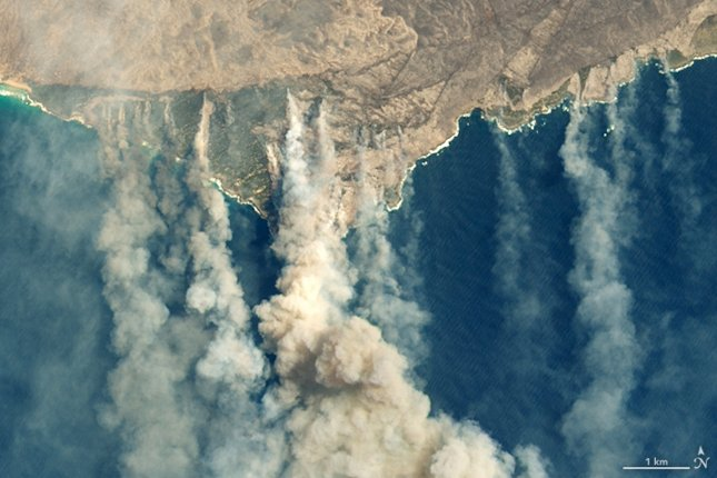 A satellite image from January shows burned land and thick smoke over Kangaroo Island, Australia. The World Wide Fund said Monday that some 41,000 koalas on the island were negatively impacted by the fires. Photo by NASA Earth Observatory/EPA-EFE