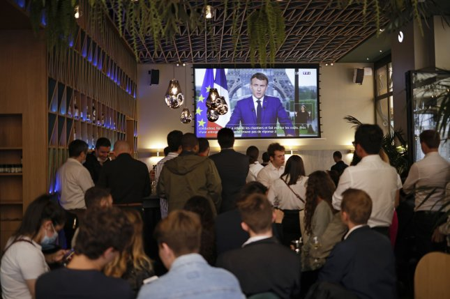 Bar customers in Paris watch French President Emmanuel Macron's televised address Monday announcing enhanced measures to fight the spread of COVID-19. Photo by Yoan Valat/EPA-EFE