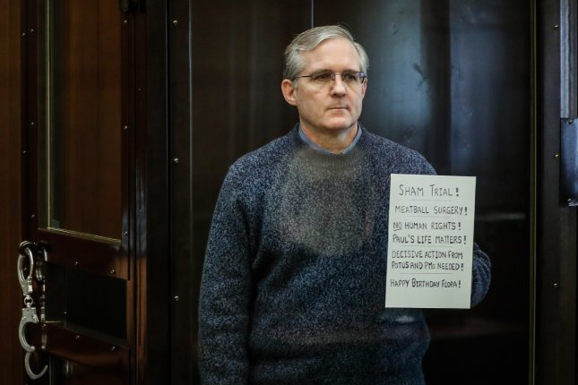 U.S. citizen Paul Whelan holds up a sign denouncing the legal proceedings against him as he stands inside the defendant's cage before hearing the verdict of his espionage trial at the Moscow City Court on Monday. Photo by Uri Kochetkov/EPA-EFE