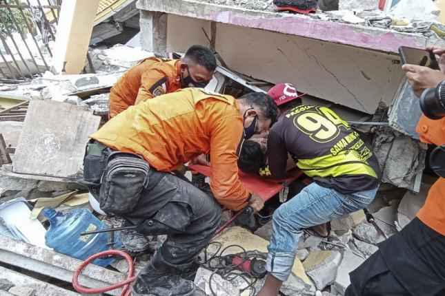 Indonesian rescuers pull a survivor out of the ruin of a collapsed building following a 6.2-magnitude earthquake in Mamuju, West Sulawesi, Indonesia early Friday. Photo by EPA-EFE