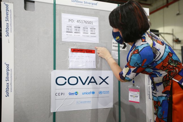 A health worker checks a shipment containing COVID-19 vaccines delivered via the COVAX program, at Noi Bai International Airport in Hanoi, Vietnam, on April 1. Photo by Luong Thai Linh/EPA-EFE