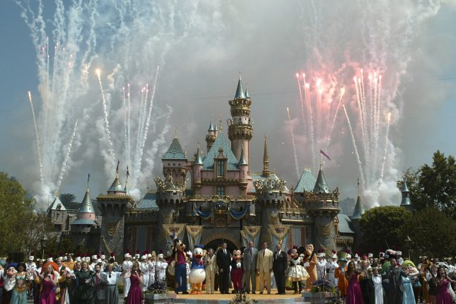 Officials are surrounded by Disney characters as fireworks go off as part of Disneyland's 50th birthday party in Anaheim, California, on July 17, 2005. Disneyland is opening a mass coronavirus vaccination center this week. Photo by Brendan McDemid/EPA