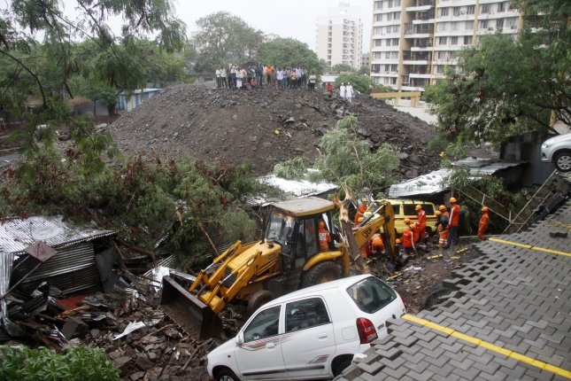 Members of the Indian National Disaster Response Force team works at the site of a wall collapse in Pune, India, Friday. Photo by EPA