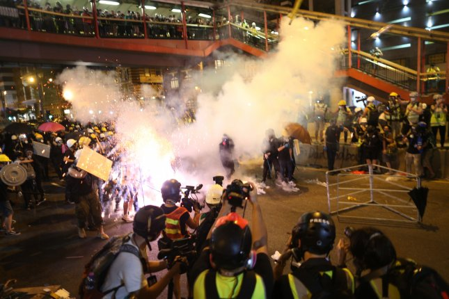 Riot police shot tear gas at demonstrators protesting actions by police against people participating in earlier protests related to an extradition bill in Hong Kong. Photo by Jerome Favre/EPA