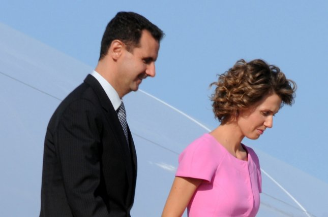 Syrian President Bashar al-Assad (L) and his wife Asma al-Assad are shown upon their arrival at Tunis Carthage Airport in Tunis on July 12, 2010. The president's office announced Monday that the couple has tested positive for COVID-19. File photo by EPA-EFE/STR