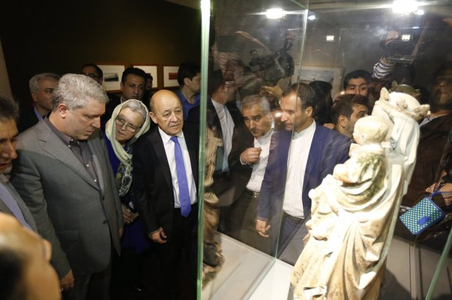 French Foreign Minister Jean-Yves Le Drian (C) and Vice President of Iran Head of Cultural Heritage Ali Asghar Mounesan (L) tour an exhibition of 50 artworks from the Louvre at the National Museum in central Tehran. Photo by Abedin Taherkenareh/EPA