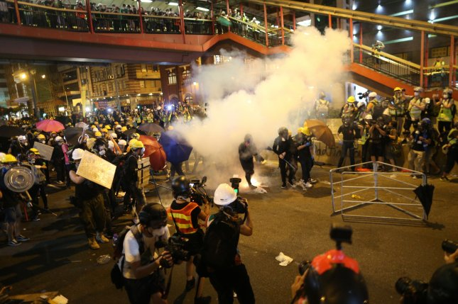 Riot police shoot tear gas late Sunday while anti-extradition bill protesters rally in Hong Kong. Photo by Jerome Favre/EPA-EFE