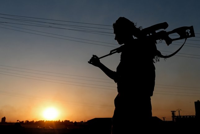 A member of the Kurdish People Defence Units (YPG) patrols near the Tel Abyad border gate in northern Syria. Wednesday, Turkish President Recep Erdogan warned U.S. President Donald Trump against his decision to arm the group to fight the Islamic State. File Photo by Sedat Suna/EPA