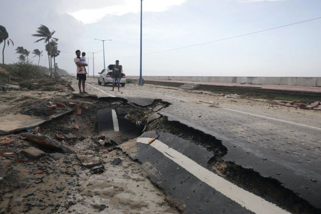 A family waits near a damaged road after Cyclone Yaas hit Digha town near Bay of Bengal, India, on Thursday. Photo by Piyal Adhikary/EPA-EFE