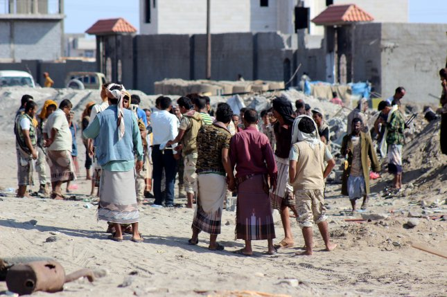 Yemeni civilians and soldiers stand at the site of suicide bombing Sunday near a military base in the southern province of Aden, Yemen. Photo by European Pressphoto Agency