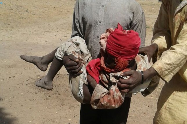 A man carries a wounded child in the aftermath of a bombing allegedly carried out by the Nigerian Army at a government-run camp for internally displaced persons in Rann, Nigeria, on Tuesday. Dozens of civilians, medical personnel and military troops were killed and wounded in the attack, which was reportedly based on flawed intelligence. Photo courtesy MSF/European Pressphoto Agency