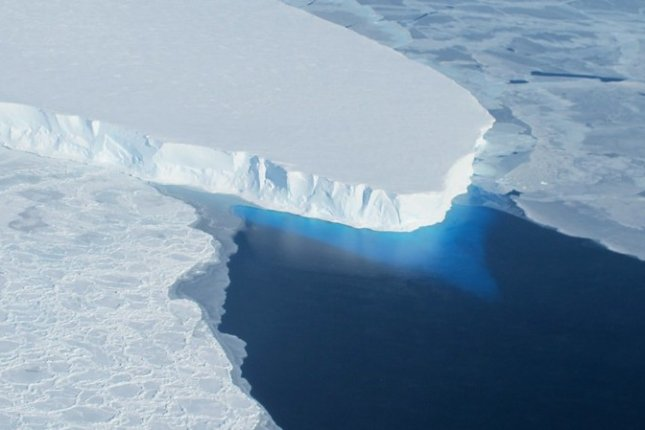 The calving front of Thwaites Ice Shelf, with a view of the ice below the water's surface, as seen from the NASA DC-8 in 2012. Photo by James Yungel/NASA/Flickr