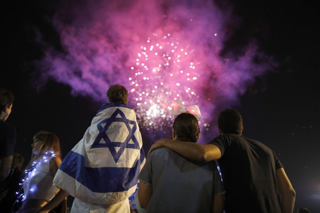 Israelis wearing Israeli flags watch fireworks during celebrations Monday for the 69th Israel Independence Day on Rabin Square in Tel Aviv, Israel. On Sunday, Israel's Cabinet endorsed legislation that declares the State of Israel is the national home of the Jewish people. Photo by Abir Sultan/EPA